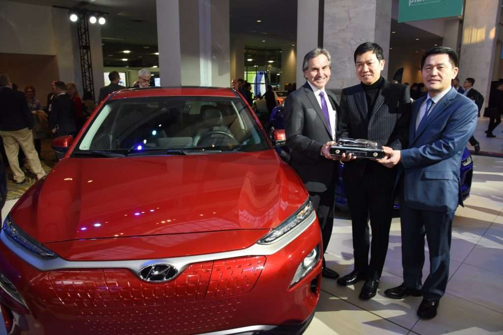 Hyundai Kona EV with executives holding the NACTOY trophy for winning the 2019 Utility Vehicle of the Year award